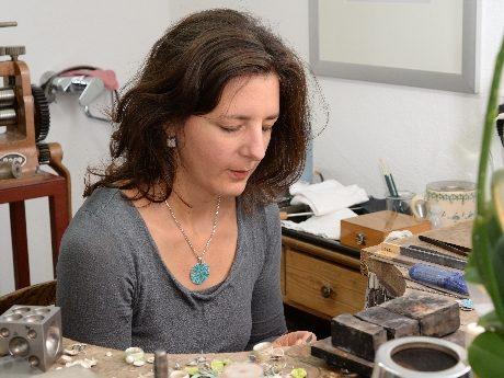 Katrin Köhler an ihrem Werkbrett in der Emaille-Schmuck-Werkstatt